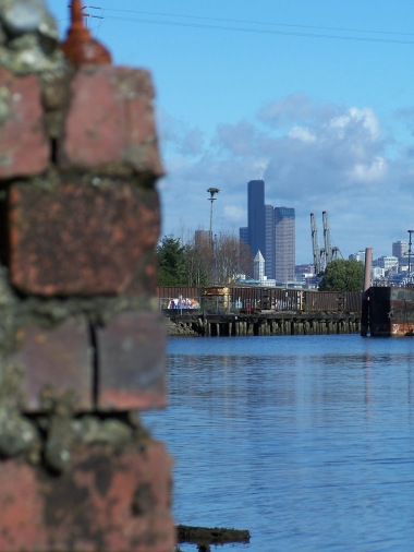 Peeking around an old brick wall at Seattle and the box car area