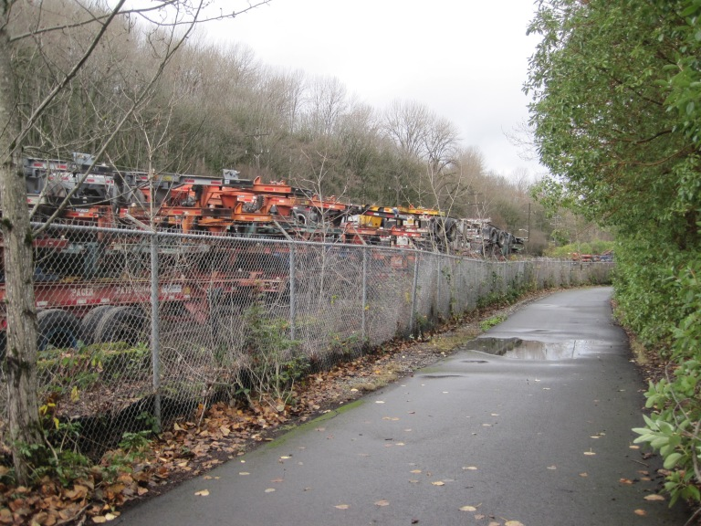 Trailers stacked beside Duwamish River Trail across from Kellogg Island